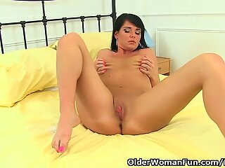 English milf Leah takes off her dress and fingers her fanny